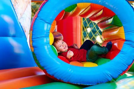 Gelukkige kinderen spelen op opblaasbare attractie speeltuin Stockfoto