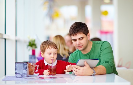 father and son with tablet in colorful cafe photo