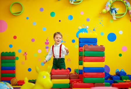 play room: laughing kid having fun in kindergarten