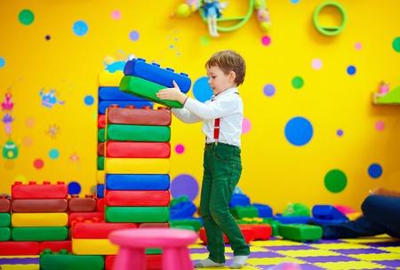 happy kid building blocks in kindergarten photo