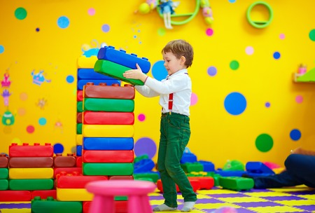 nursery school: happy kid building blocks in kindergarten