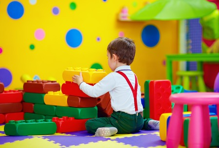 early education: happy kid playing with toy blocks in kindergarten