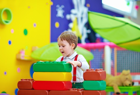 cute kid playing with toys in nursery room photo