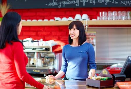 웨이트리스가 커피 숍에서 고객을 제공합니다