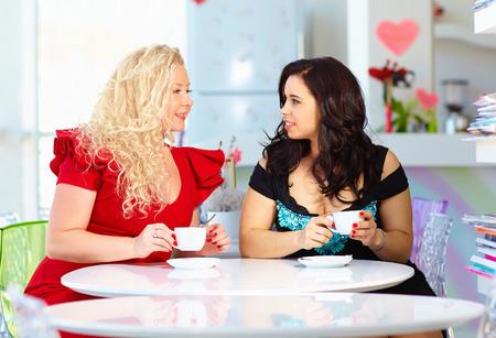 プラスのサイズのカフェに座っている女性
