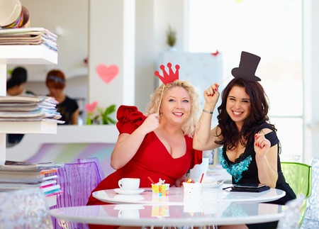 curvy: plus size women friends enjoying life, having fun in cafe Stock Photo