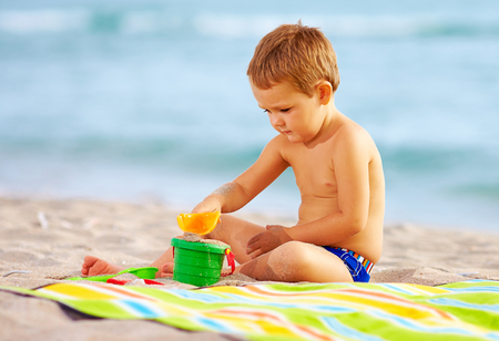 beach toys: cute kid playing with toys in sand on the beach