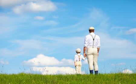 father and son look beyond the horizon photo