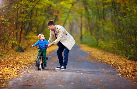 아버지는 아들에게 자전거 타기를 가르칩니다.