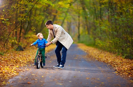 teaches: father teaches son to ride the bicycle
