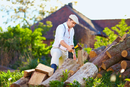 man chopping wood on the backyard photo