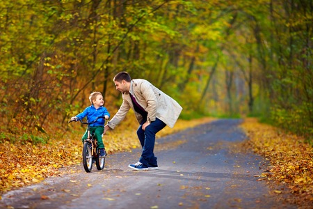 niños en bicicleta: padre enseña a hijo a andar en bicicleta Foto de archivo