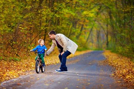vader leert zoon aan de fiets gaat rijden Stockfoto