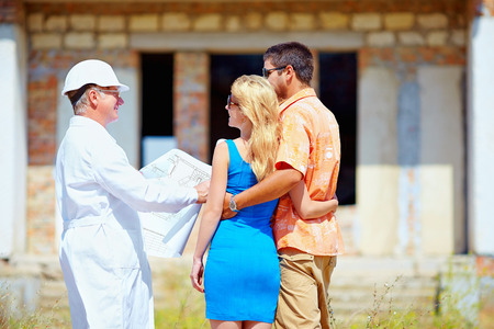 young couple and architect discussing house project photo