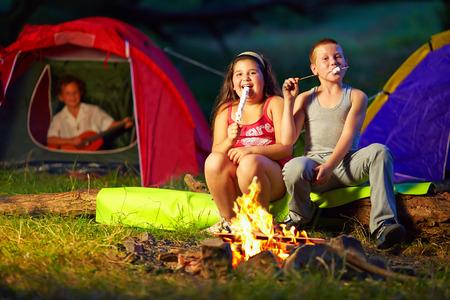 campamento: felices los niños asar malvaviscos alrededor de la hoguera