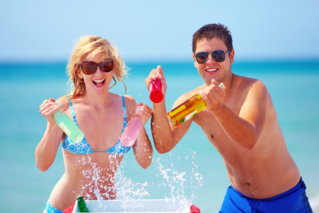chilling: happy friends holding chilling drinks on the beach Stock Photo