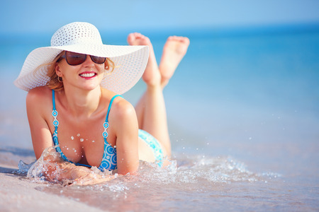 surf girl: beautiful girl lying in surf on the beach