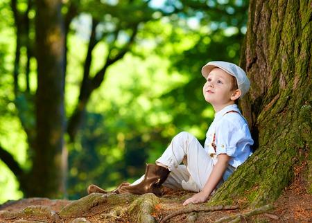 niedlichen Jungen sitzen unter einem alten Baum im Wald