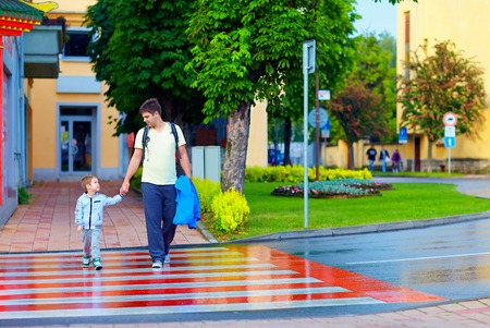 pedestrian crossing: father and son crossing the city street on crosswalk