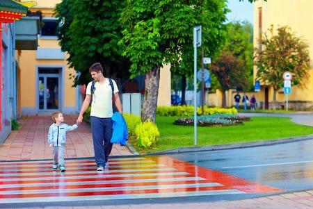vader en zoon het oversteken van de straat in de stad op zebrapad Stockfoto