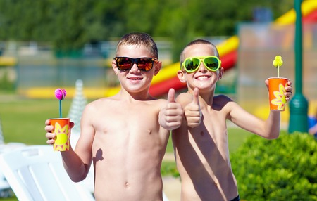 two thumbs up: happy teenage boys showing thumbs up in aquapark