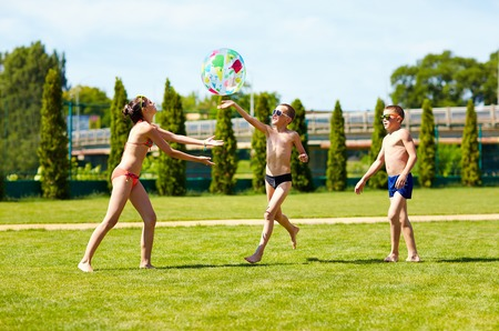 recreate: group of teenage kids playing with ball on summer lawn
