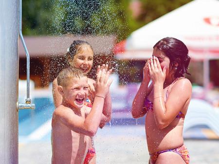 excited teenage friends under summer shower photo