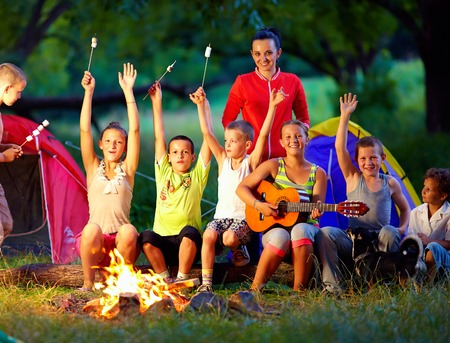 campfires: happy kids singing songs around camp fire