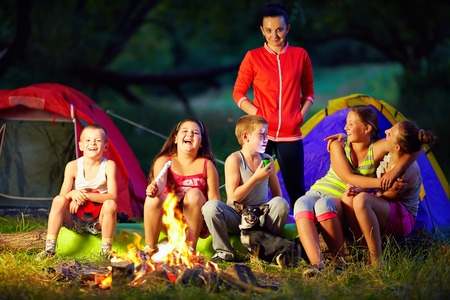 forest fire: happy kids telling interesting stories around campfire