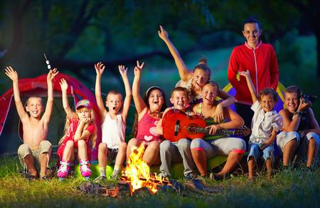 obóz: szczęśliwe dzieci śpiewają piosenki wokół ogniska