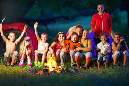 happy kids having fun around camp fire photo