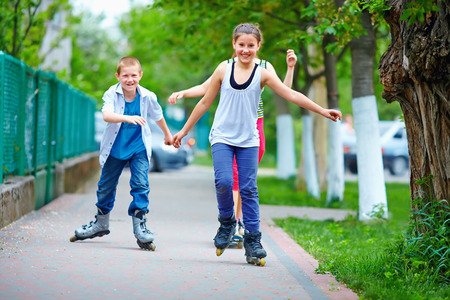 roller skating: happy teenage friends playing outdoors