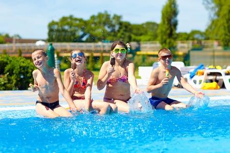 comiendo helado: amigos felices comen un helado y disfrutar de verano en la piscina