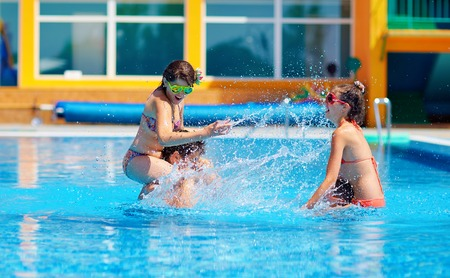 excited friends having fun in pool, water fight Stock Photo
