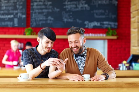 two male friends sitting in cafe photo