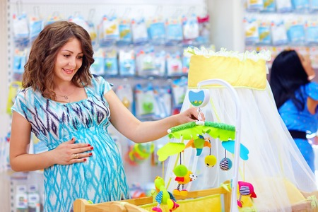 pregnant woman buying cradle with mobile toy for baby photo