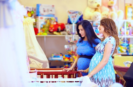 pregnant women choosing cot for baby Stock Photo