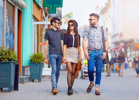 happy crowd: stylish friends walking the city street