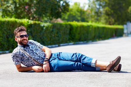 shoe model: cheerful young adult man lying on the road Stock Photo