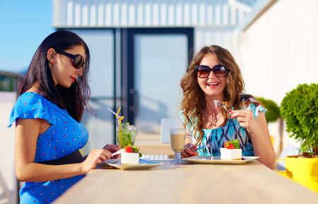 happy female friends enjoying cakes in cafe, pregnant women photo