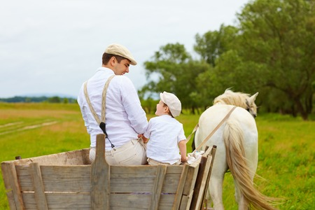 father and son, farmers ride a horse cart photo