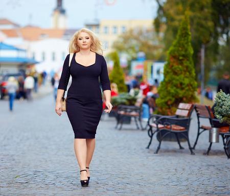 mujer gorda: mujer con sobrepeso conf�a en caminar por la calle de la ciudad Foto de archivo