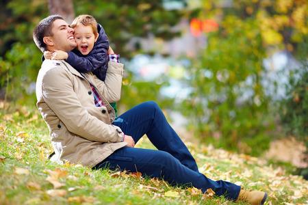 glückliche Vater und Sohn Spaß im Herbst Park