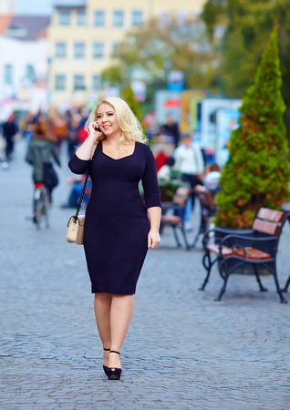 attractive overweight woman talking on the phone in the city