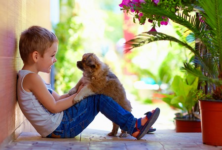 excited boy playing with beloved puppy photo