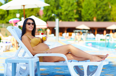 recreate: happy pregnant woman relaxing on sunbed