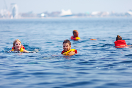 people in life jackets swimming in open sea photo