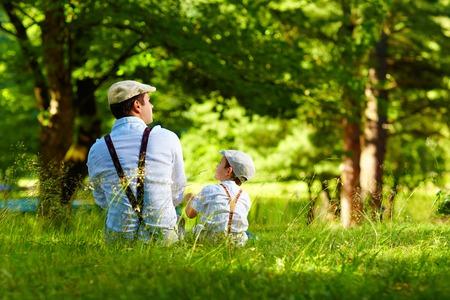 padres hablando con hijos: padre e hijo sentados en el césped del bosque Foto de archivo