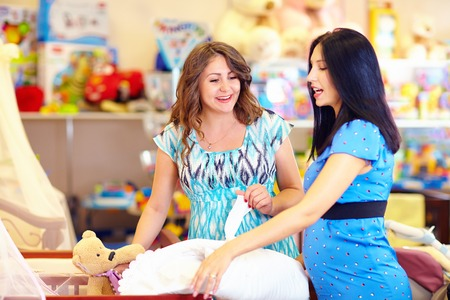 pregnant women choosing goods for baby photo