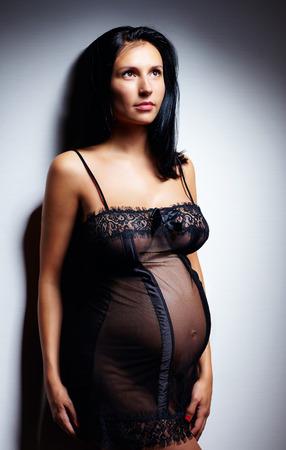 nude pose: sensual pregnant woman in nightie Stock Photo